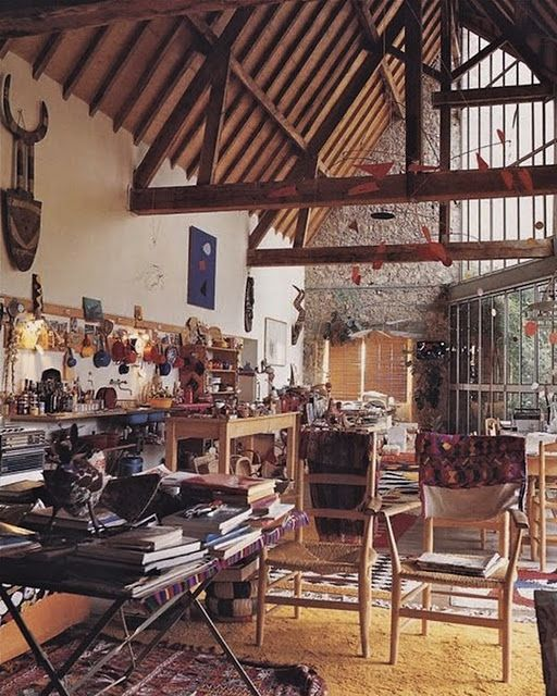 Alexander Calder's house.  Mobile. Textiles on every surface. Calder painting and African masks on wall. Small Calder sculpture on table. Books everywhere.  All images from the book Calder at home.
