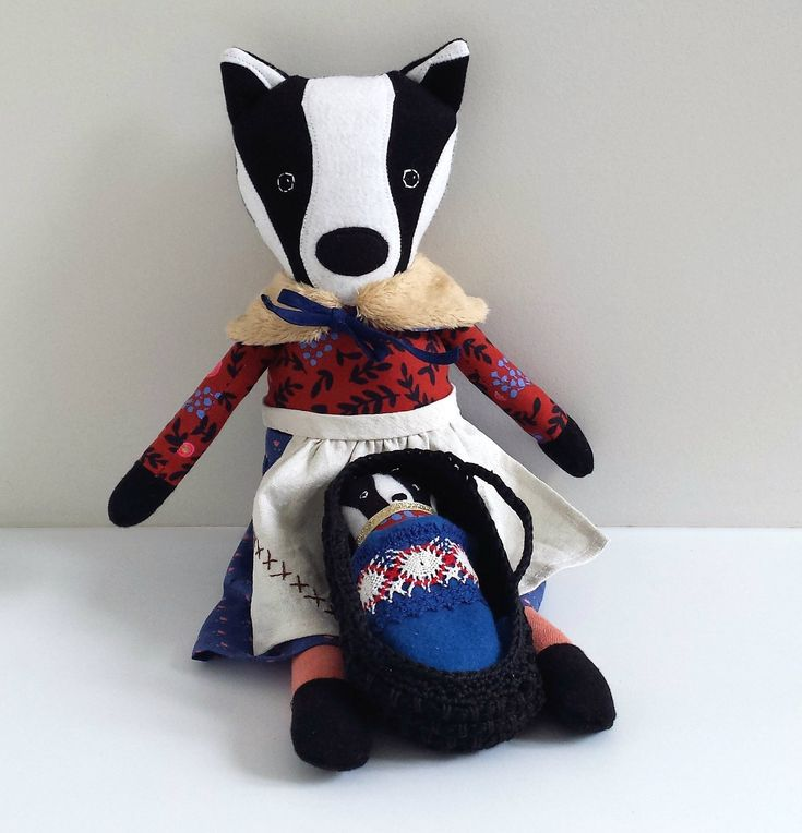 This original handmade badger doll is named Bethany and she has a cub that likes to sleep in her Moses basket.Bethany measures approximately 46 cm (18 inches) tall from tip of her ears to toes. She has a faux fur tail.She wears a pretty blue skirt and a reversible wrap/shawl. She also wears an apron made from up-cycled vintage linen.The cub is approximately 14 cm (or 5.5 inch) tall and has a little black faux fur tail.Bethany has buttons that secure her arms to her body an...