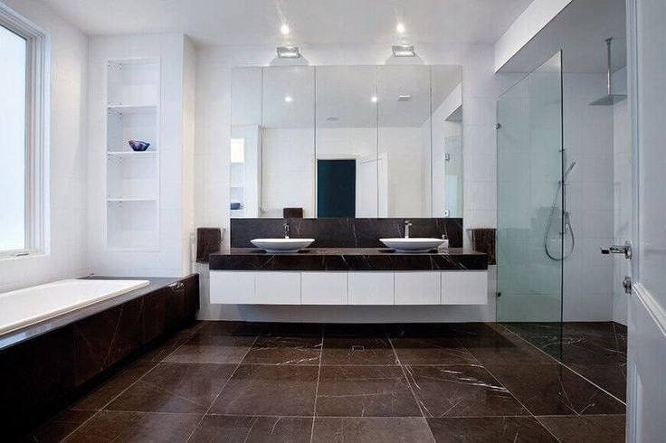 Die robuste Marmor Fliesen ist auf den Boden, rund um die Badewanne und auf der Eitelkeit Zähler für eine ansprechende Symmetrie gelegt.