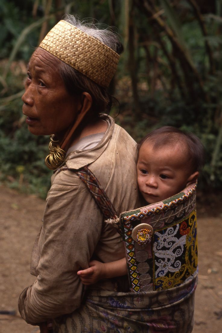 Mother with ear lobe decoration and with child in pouch | Apo Kayan, Kalimantan (Borneo), Indonesia