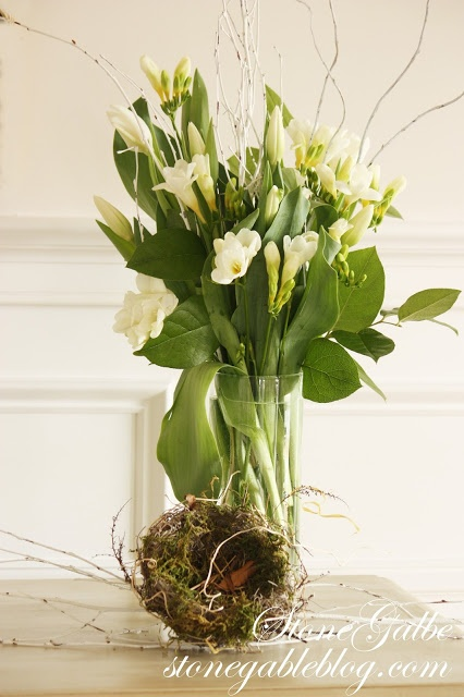 Spring arrangement using white tulips, freezia with green leaves and sprayed white twigs along with a birds nest, create a spring vignette.