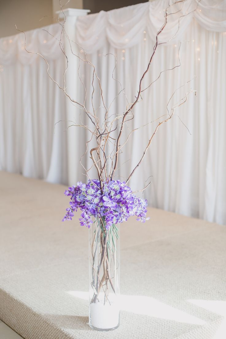 Purple florals in tall glass cylinders with branches #WeddingDecor