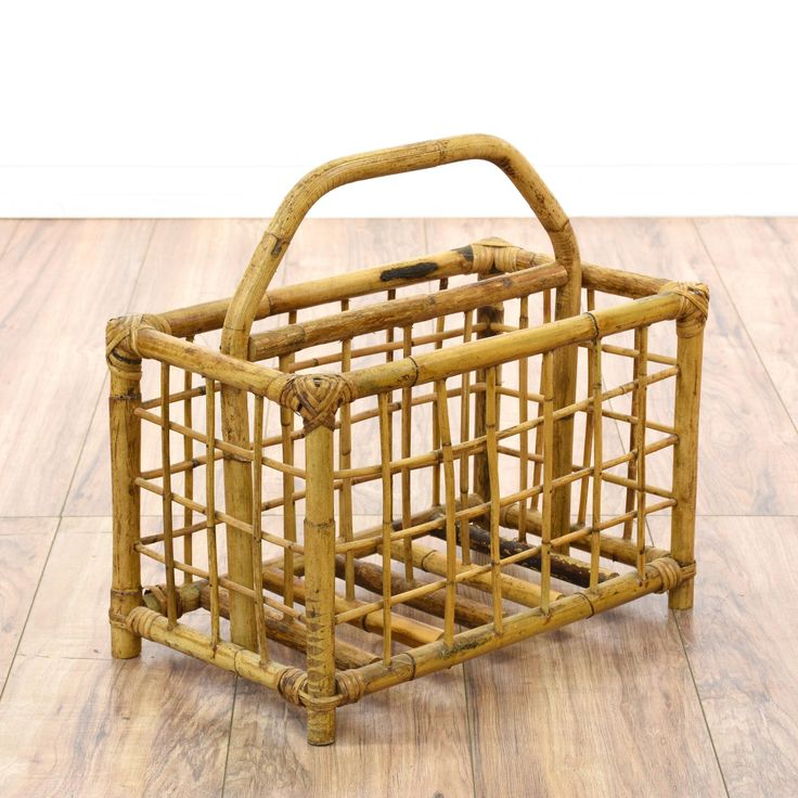 This tropical magazine rack is featured in a bamboo with a raw light wood finish. This bohemian magazine holder has a curved handle top, woven sides and 2 storage slots. Great for storing knitting supplies! #bohemian #storage #magazinerack #sandiegovintage #vintagefurniture