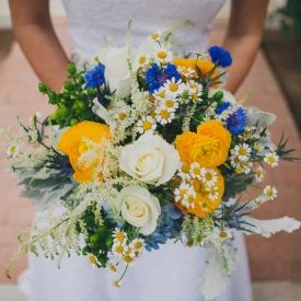 This lovely country-chic wedding is filled with wildflower bouquets, mismatched bridesmaids in blue with top knots, and lots of love.