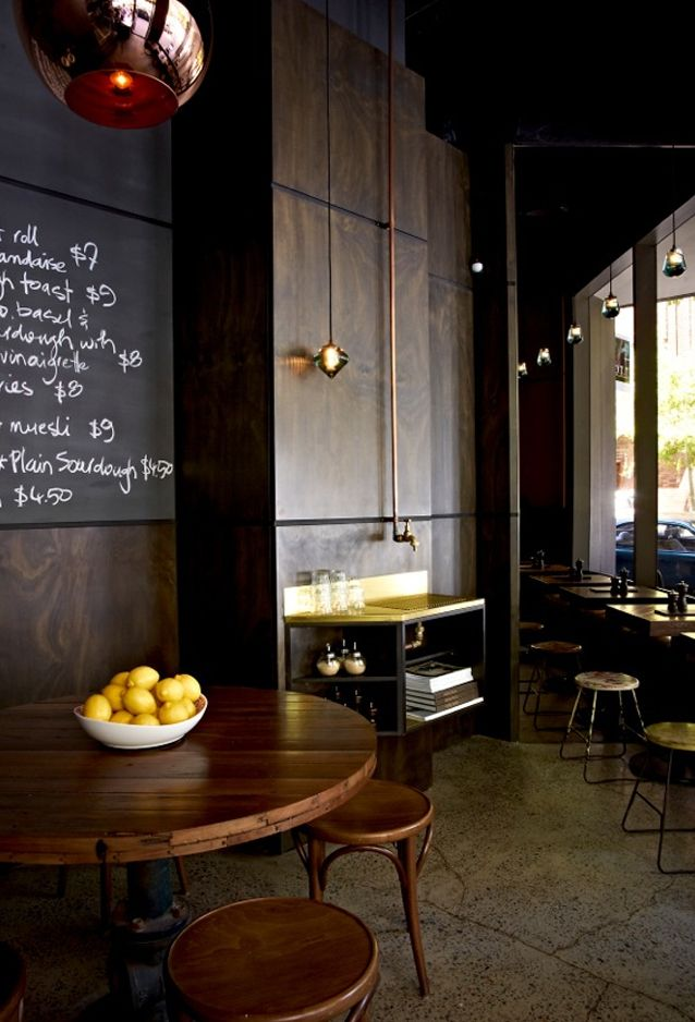 Metallic finishes – such as copper, brass and gold – contrast with the stainless steel finish in the kitchen and serving areas, while dark timber wall panels and Tom Dixon glass pendant lights add a touch of luxury - Toby's Café & Wine Bar in Potts Point