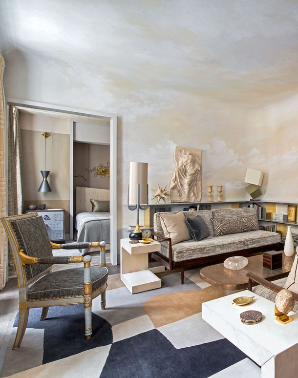 Classic Jean-Louis Deniot palette: gray, buff, straw, gold, petrol. Stone tables ground the space and add organic texture.
