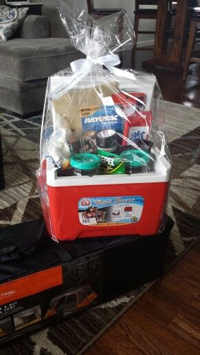 Camping basket and tent. Smores, drink cups, flashlight, bug spray, trail mix, wet wipes, and a lighter. Place items inside a mini cooler.