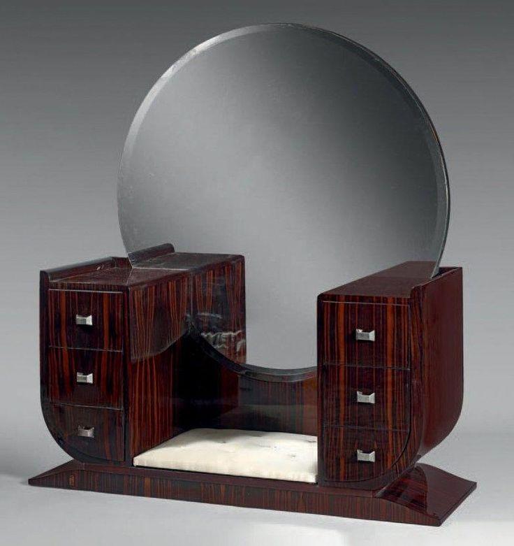 French Art Deco: TRAVAIL FRANÇAIS de 1930. Coiffeuse en placage d'ébène de macassar,  deux caissons latéraux à trois tiroirs, glace circulaire à fond de miroir, base latérale en doucine, poignées de tirages en métal chromé.