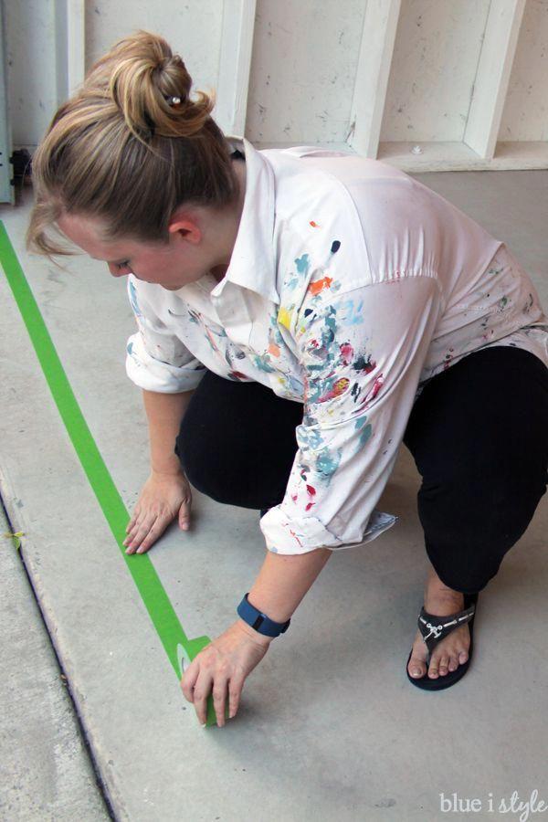 Taping along garage door line before applying metallic garage floor coating