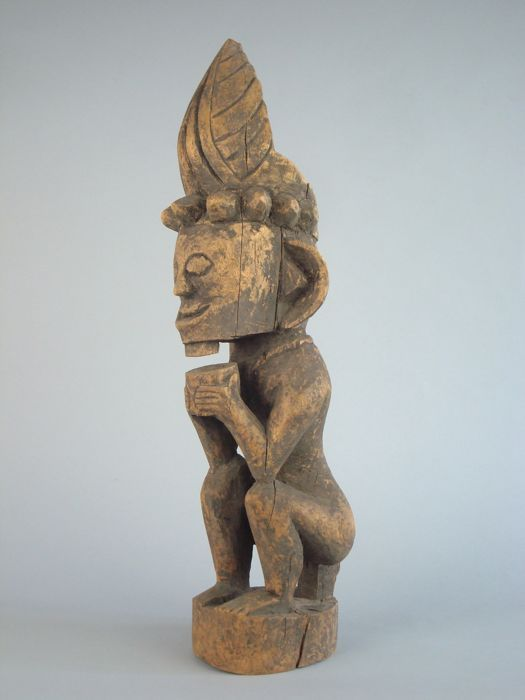 Voorouder figuur Siraha Salawa - Nias - Sumatra - Indonesië  Mannelijke voorouder figuur met een donkere knapperige patina zittend op een klein krukje.De wapens produceren een 'W'. De handen voor de borst houden een kopje. De ogen zijn amandel gevormd de baard is gestileerd. De mannelijke sieraden bestaat uit een gestileerde ketting en een oor ornament in het rechter oor. Op het hoofd is een kroon met gebeeldhouwde palmbladeren. Aan de voet van de kroon is een hoofd-band met conische punten…