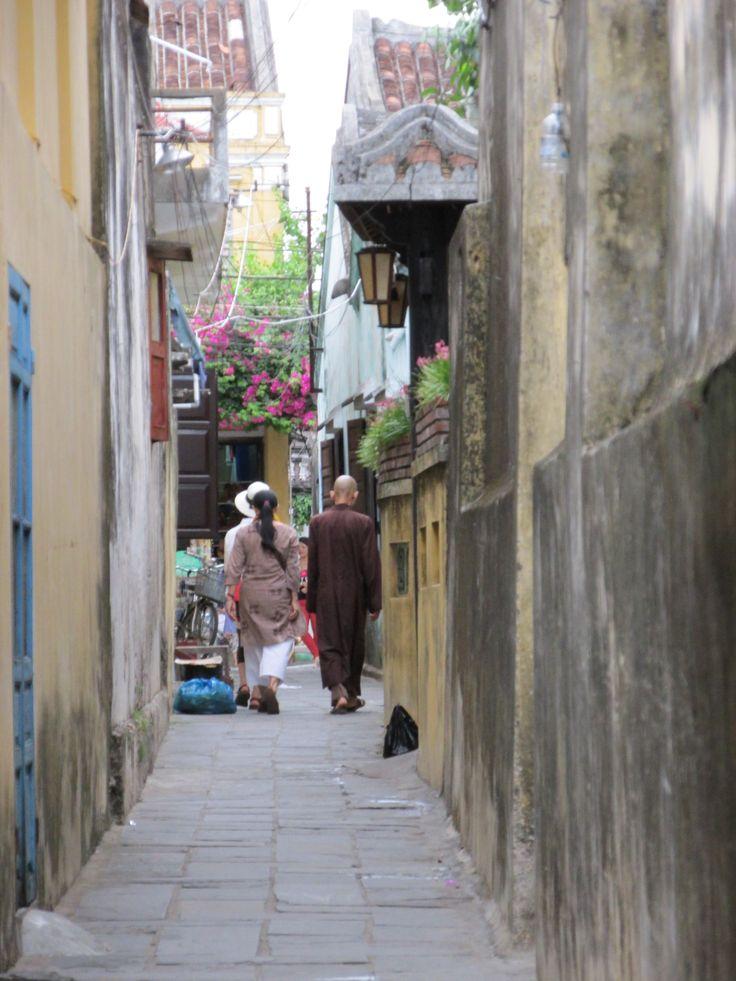 Monk walking down an alley in Hoi an Vietnam