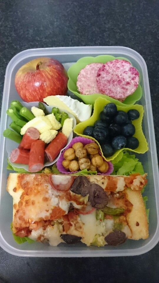 Pizza, roasted chickpeas, blueberrird, twiggy sticks, beans, baby asparagus, baby corn, camembert cheese, purple carrot mini rice cakes, apple.