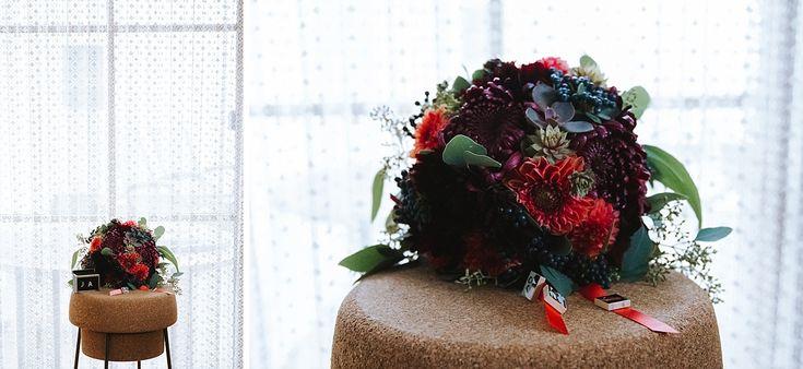 Ein Brautstrauß mit Dahlien, Sukkulenten, Eukalyptus, Beeren, Chrysanthemen und Schokoblume.
