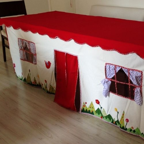 Toalha de mesa-cabaninha, da Bitôô Ateliê. A peça, criada artesenalmente, é feita com tecido resistente e sob medida para se adequar a mesa desejada. Além disso, todos os detalhes ?porta, janelas, cortinas e etc.?são personalizáveis. Os preços variam de acordo com o tamanho da mesa e vão de R$ 260 a R$ 430. O produto pode ser encontrado na feira Baby Bum Pocket (http://babybumpocket.com.br/sao-paulo), que acontece de 30 de novembro a 3 de dezembro de 2015, em São Paulo