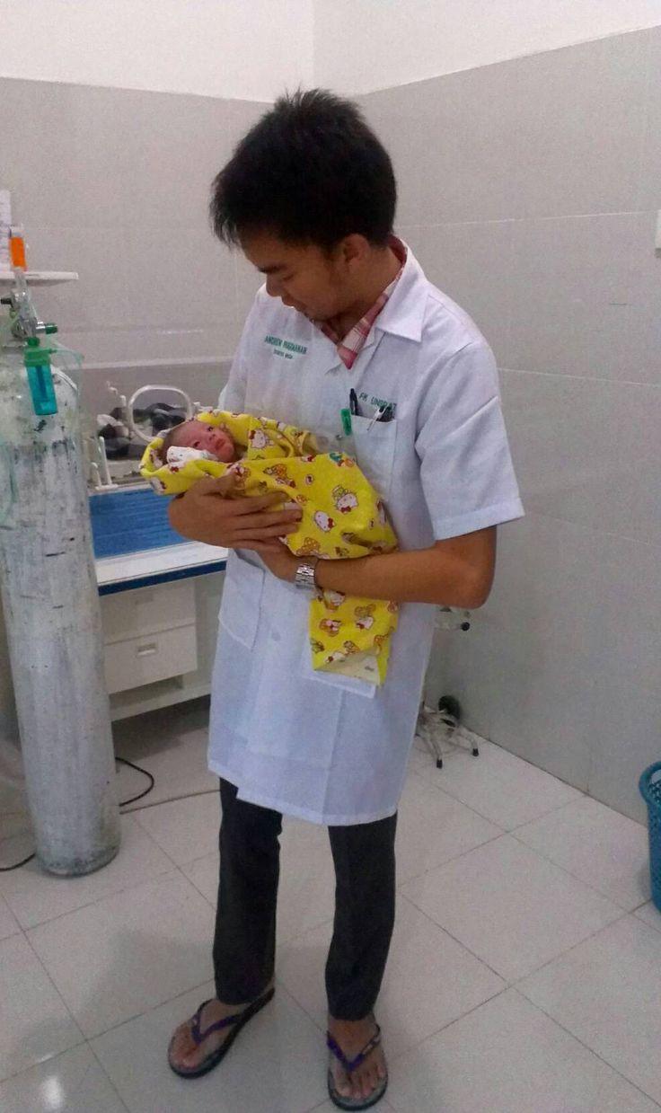ANDREW CHRISTIAN PANGEMANAN  - holding a newborn baby
