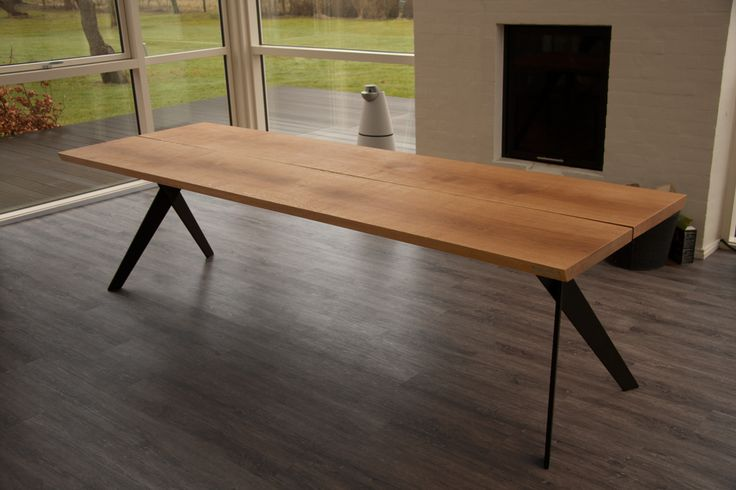A dining table made of oak planks and Bruun & Buus designed table legs.