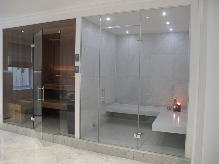 This stylish steam room has white Corian benches and large format tiles to the walls. The adjacent sauna is made from medium Thermo Alder, the darkness creating a stunning contrast with the steam room. Backrest lighting adds a warm ambience to the sauna and both rooms are finished with frameless glass to accentuate the feeling of space and light.