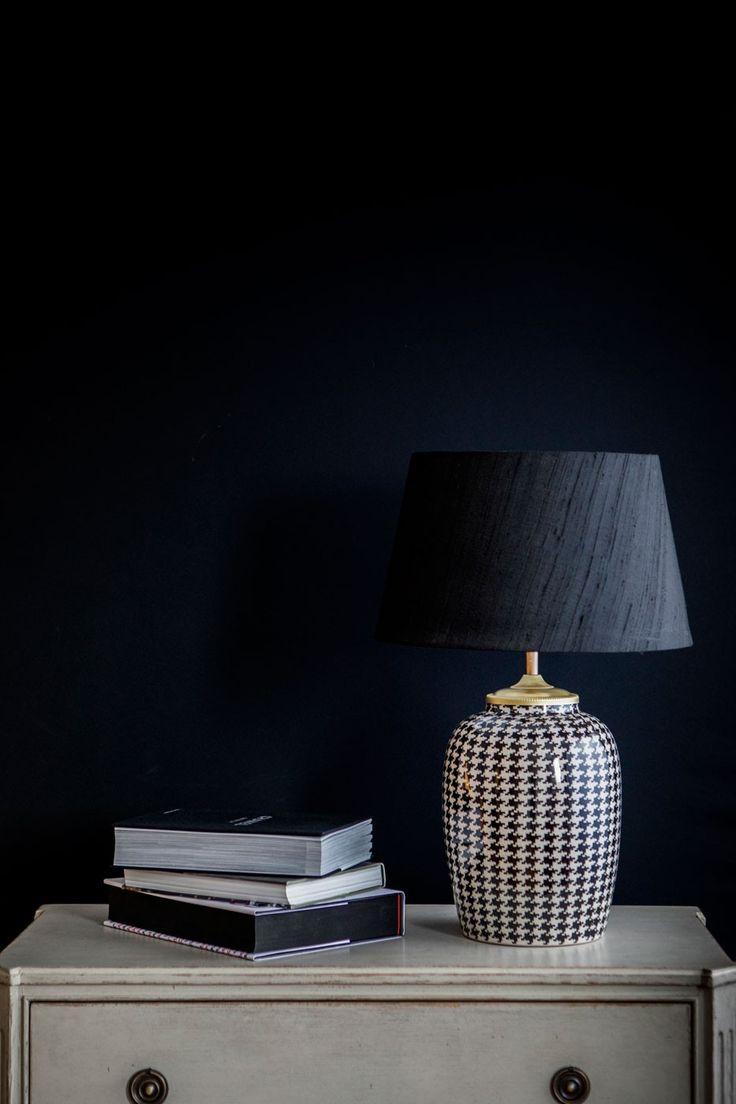 Vedder är en sobert utformad bordslamapa i stengods. Foten är dekorativt målad i ett klassiskt svart/vitt hundtandsmönster.