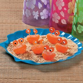 1. Cover a plate or tray with crushed up graham crackers for the sand. 2. Insert 2 toothpicks into the flat side of a gummy orange slice and attach circular orange gummies to the top of the toothpicks. 3. Using edible frosting, create eyes on the gummies to complete your treats. Lobster+Jelly+Treats+Idea+-+OrientalTrading.com