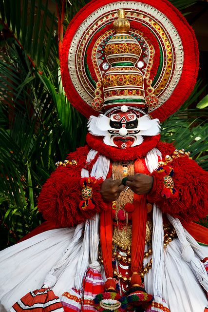 Portrait of Kathakali dancer in full make-up and costume portraying Chuvanna Thadi, wearing elaborate headgear called Mudis and demonstrating the double hand movement known as Samyutha Mudras.