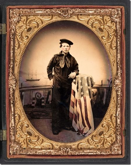 Unidentified young sailor in Union uniform with American flag in front of backdrop showing naval scene.    Donated to the Library of Congress 2010 by Tom Liljenquist; Liljenquist Family Collection of Civil War Photographs.