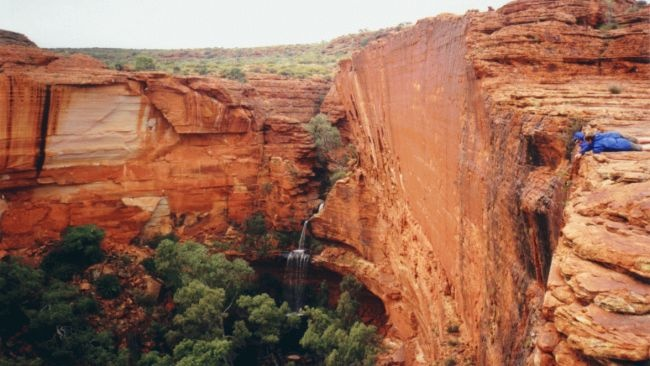 Located in Watarrka National Park in Australias Northern Territory, Kings Canyon lies on the western end of the region known as the George Hill range and is home to several hiking trails, including a 3- to 4-hour-long rim loop walk that features a steep ascent called Heart Attack Hill.  Massive red sandstone walls rise more than 300 feet above the canyon, through which Kings Creek flows at the bottom. Inside the park, visitors can hike to the Garden of Eden, a water hole surrounded by lush