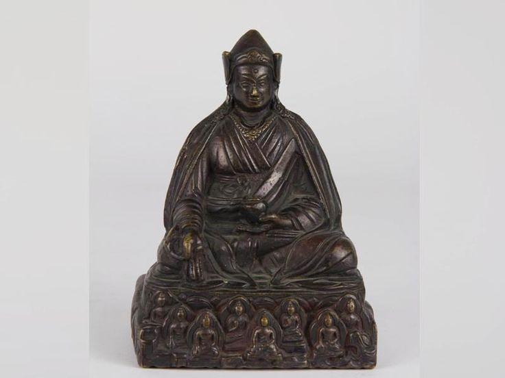 """Padmasambhava, Nepal, 18. Jh., Bronze, Padmasambhava (übersetzt: Lotosgeborener, auch Guru Rinpoche, gilt als Begründer des Buddhismus in Tibet zur Zeit des Königs Thrisong Detsen), im Lotussitz mit dicker Robe und einer Schale in der einen Hand, und einer Myrobalan Frucht in der anderen Hand sitzend Haare dreigeteilt über den Schultern und den Rücken fallend, eine Pandita als Kopfbedeckung, Sockel mit den """"Acht Manifestationen Padmamasambhavas""""mit Heiligenschein und Mandorlas umgeben…"""