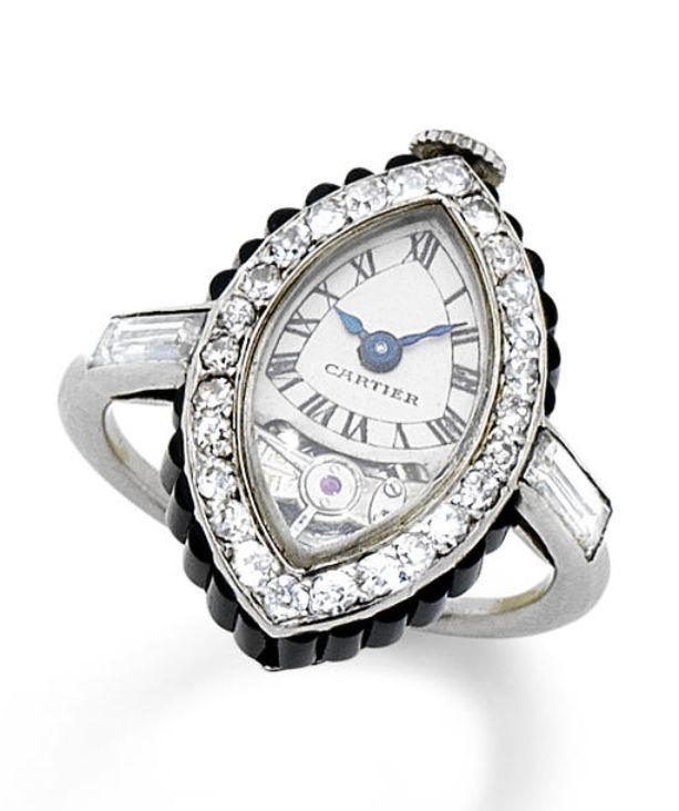 "A rare art deco onyx and diamond ""Montre Bague Navette"" keyless ring watch, by Cartier, circa 1920 The ""ship"" case set with shaped onyx batons, the dial with Roman numerals, blued steel hands and visible balance, within a single-cut diamond bezel, the crown decorated with rose-cut diamonds, mounted in platinum, dial signed Cartier,"