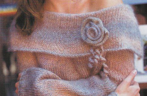 Un maglione lungo e caldo, semplicissimo da realizzare a maglia rasata e impreziosito dal più romantico dei fiori, una morbida rosa in maglia.