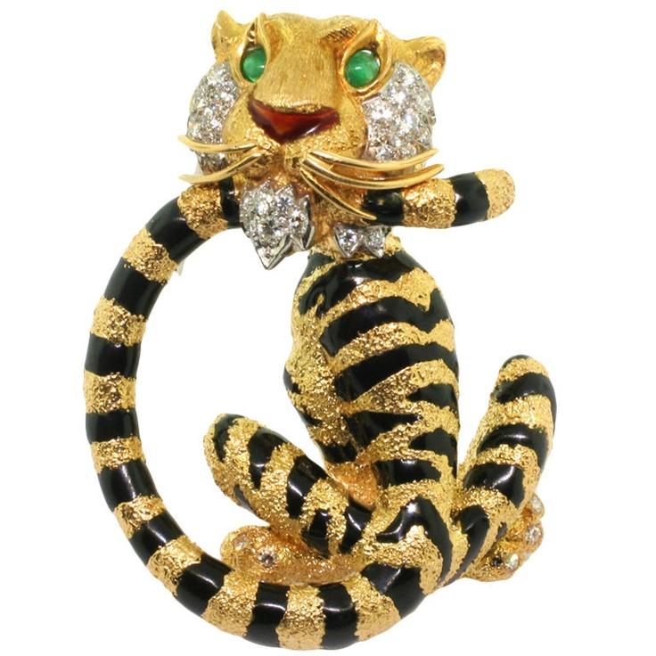CARTIER. A Diamond Emerald and Enamel Brooch.  France  Circa 1970's  Designed as a tiger turning round to bite his tail. The body applied with black enamel stripes, the eyes accented with emerald cabochons, the cheeks, chin and toes embellished with brilliant-cut diamonds, signed Cartier Inc, circa 1970, Stamped 750 for 18ct gold.  SOLD.