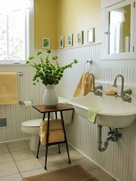 Farmhouse bathroom with yellow walls and wainscoting for Small yellow bathroom ideas