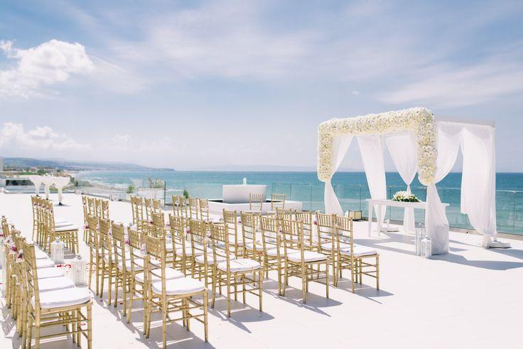 Breath-taking luxury hotel wedding ceremony set up with wedding canopy decorated with seasonal flowers. MOMENTS in Crete. www.weddingincrete.com