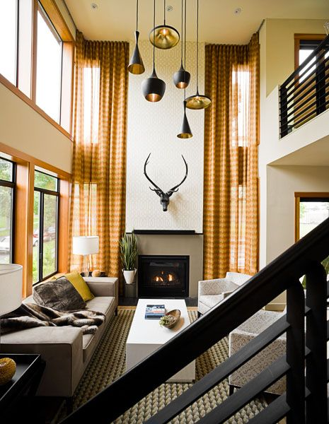 pendants + metal staircase + fireplace design + floor to ceiling windows and drapery + neutral patterns in living room via john granen