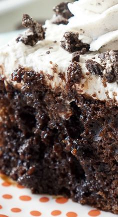 Easy Oreo Poke Cake ~ So simple to make... A rich chocolate cake loaded with Oreo pieces and drenched in chocolate syrup with a cookies and cream frosting!