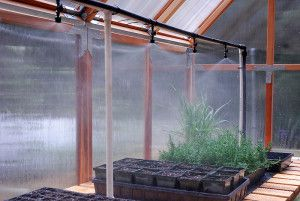 PVC stand supports water mister system over greenhouse bench.