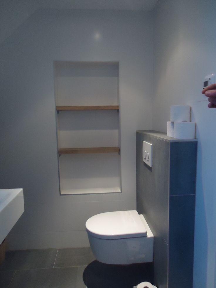 Toepassing van massief eiken (voorzien van een beschermende lak) in de badkamer d.m.v. planken als nissen.