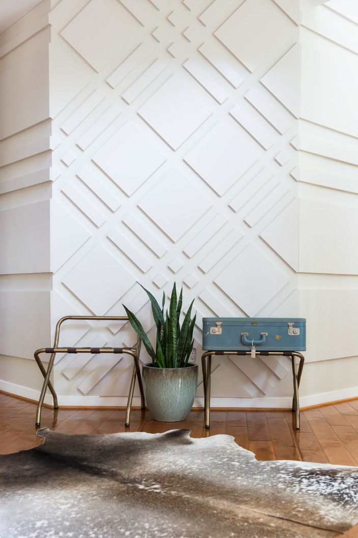 """""""Graphic wall treatments are one of my favorite elements to implement,"""" says Dana. """"They pack  a powerful punch and aren't seen in your typical house."""" In the entryway of their home, Dana and her husband crafted this all on their own from 1/2-inch-thick MDF. On the feature wall, it's in dramatic diamonds, but moving in either direction, it melts into stripes."""