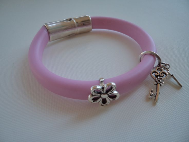 Pink bracelet made of rubber cord with hanging silver metallic cross, key and a flower.