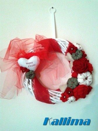 Ghirlanda in midollino bianco, decorata da nastro di iuta, arricchito da nastro in tulle,fiori in pannolenci e lana. Lo completa un cuore bianco in pannolenci augurale.
