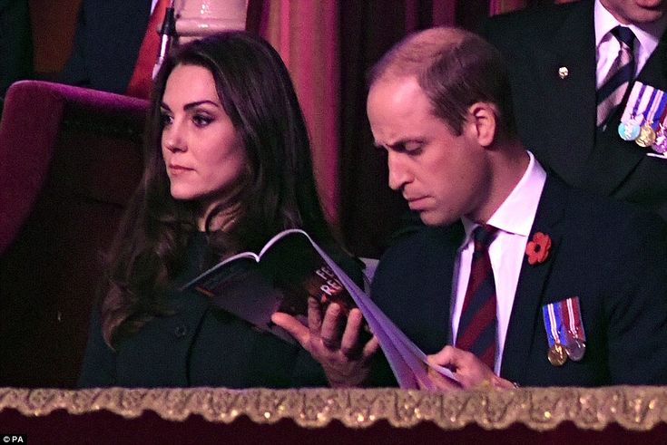 Prince William has a quick peek through the programme as the Duchess of Cambridge watches ...