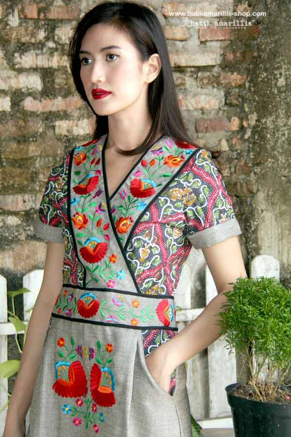 Batik   Amarillis's primavera dress with hungarian embroidery The design offers a chic take on pinafore styling with its cross-over bodice also it has a cross-over V-neck and contrast accents and zip fastening at the back of the dress.