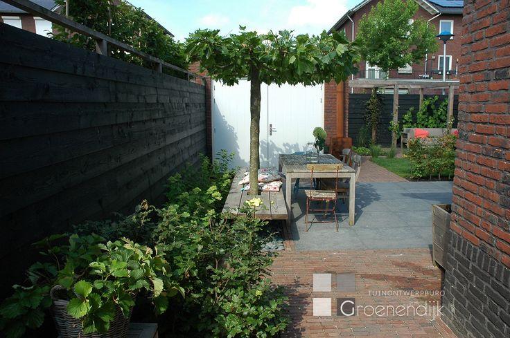Eigentijdse tuin in Culemborg met sfeervolle materialen, een 'zwevende' bank en veel ruimte