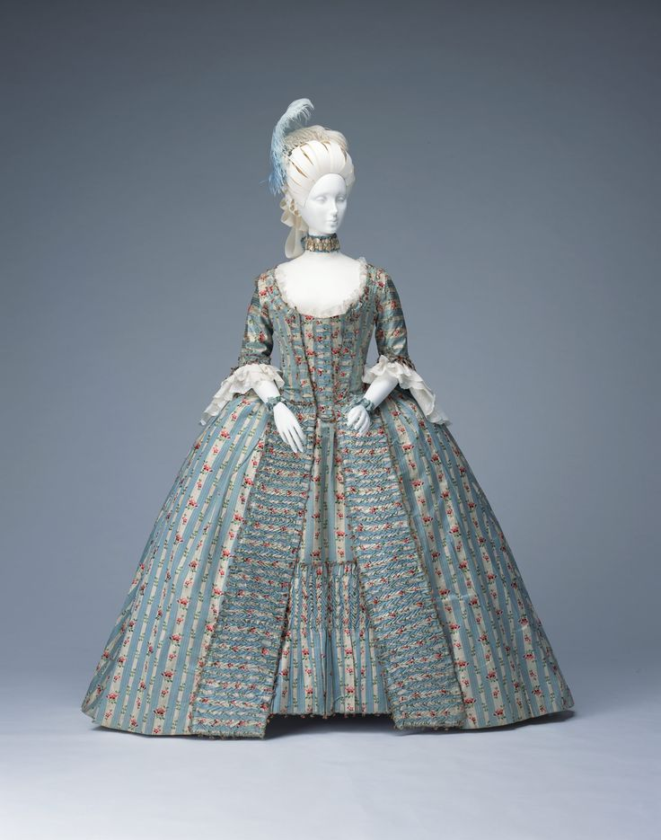 "Dress (""robe à la française"") c. 1770-1775-France. Blue Lyons silk brocade with white floral stripe; trimmed with self fabric and fry fringe; matching stomacher and petticoat. Kyoto Costume Institute"
