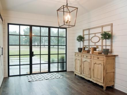 Dark hardwood floors in the downstairs dining room and entryway help provide a warm balance with the white shiplap walls.