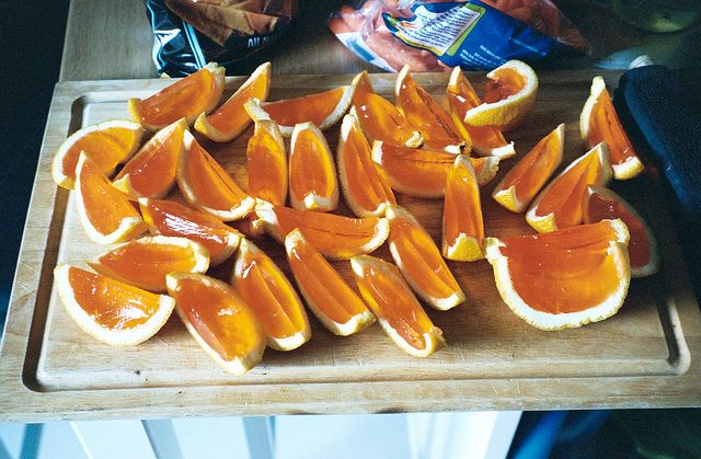 Orange Jello Shots  1) cut the oranges in half and hollow out   2) make orange jello but substitute cold water with cold vodka  3) pour spiked jello into orange 'cups' and let sit overnight  slice and serve!