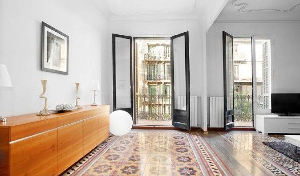 Barcelona Vacation House Rental // Living room with mosaic tiled floors and exterior-facing balconies.