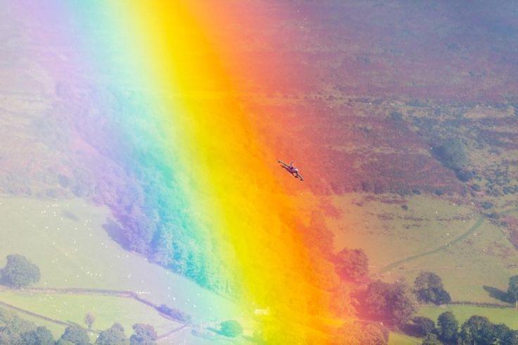 Um caça voando através de um arco-íris