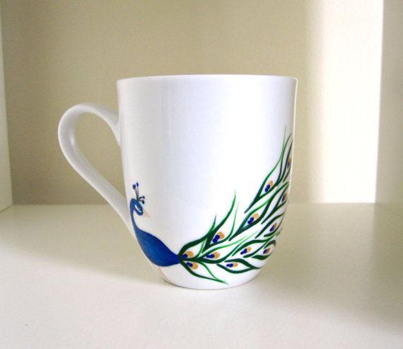 Ce paon bleu avec éclat est exhibant ses belles plumes... et qui pourrait lui reprocher ?  Jai peint mon dessin paon sur cette tasse à café en céramique avec la richesse des couleurs que nous aimons à voir dans ces oiseaux exotiques à la main. Un bleu très vif et dimensionnel compose de corps de ce paon avec beaucoup de détails comme les yeux et la tête de plumes pour presque lui donner vie. Ses plumes de paon bien-aimé semblent « swoosh » autour de la tasse à café. Formes lumineuses doré «…