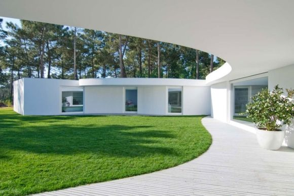 """Residential Architecture: House in Aroeira by Aires Mateus: """"..The site's hexagonal shape goes unnoticed due to the lack of fencing, which dilutes the land into the surrounding pine trees. This house covers the maximum possible area, echoing the shape of the site. It is arranged around a courtyard, articulating its spaces as an extension of this central space. Beginning from a capricious shape, this house encounters its first sharp boundary in the outline of the awning. The auxiliary zones…"""