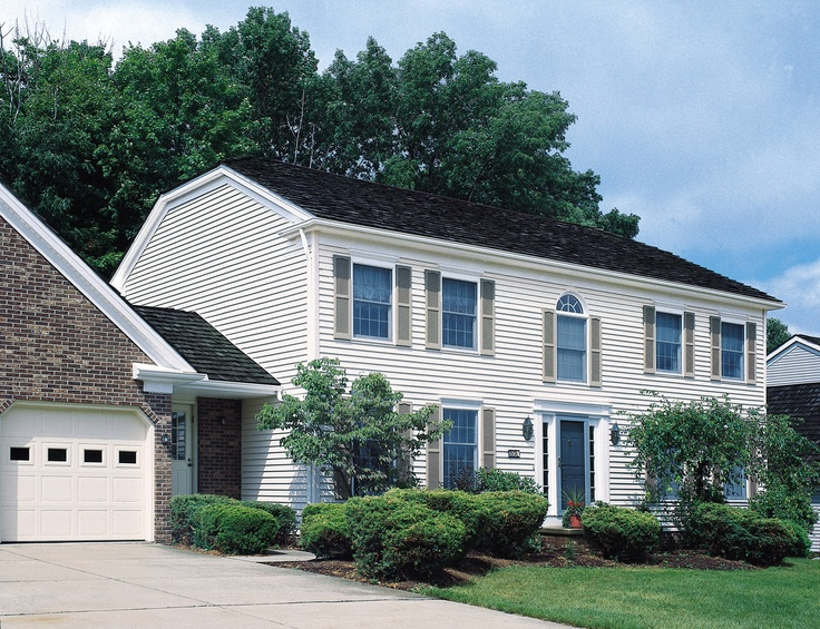 CenterLock siding shown in Maple clapboard with white vinyl window headers, maple trim accents and tan louvered shutters.